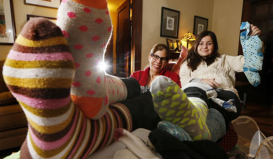 In this Nov. 18, 2014 photo, Ruth Milligan and her daughter Maggie Daiber, 10, sit with socks that need to be sorted in their Clintonville home in Columbus, Ohio. Maggie's Matches, a once-a-year effort to collect single socks, match them by size, weight and color, and donate them to sockless souls. (AP Photo/The Columbus Dispatch, Eric Albrecht)