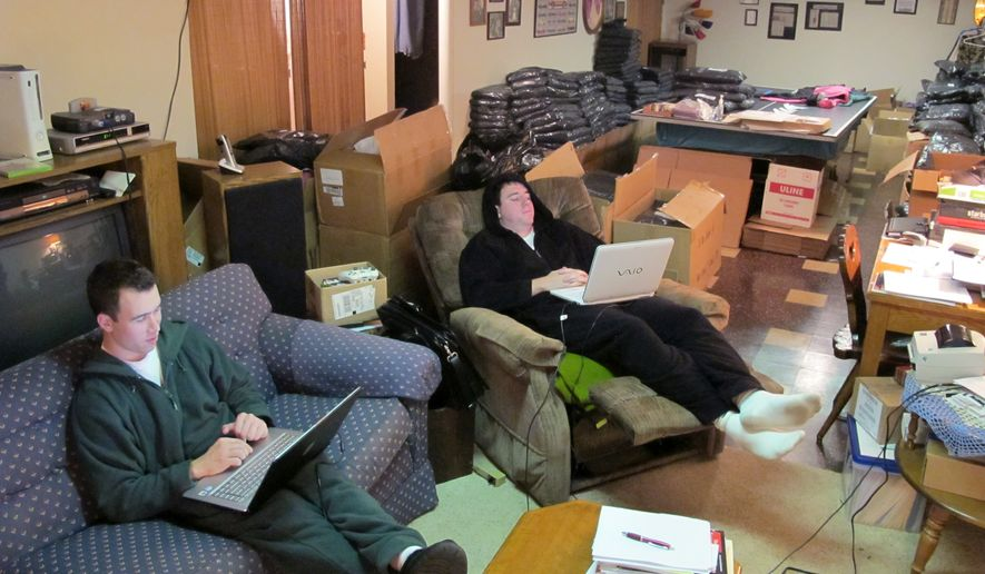 "In this Nov. 4. 2010, photo best friends Dave Hibler, left, and Tyler Galganski work out of Hibler's parents basement in Brookfield, Wis., selling adult fleece onesies. The two Wisconsin couch potatoes, 2010 finalists in ""America's Best Young Entrepreneurs"" on Businessweek's website, hope to wedge their way onto the Snuggie's sofa with a line of footless onesies with hoods called ""Forever Lazy"". (AP Photo/Carrie Antlfinger) **FILE**"