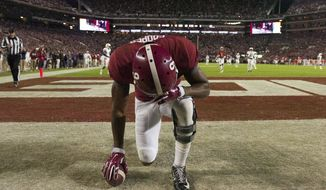 Alabama wide receiver Amari Cooper kneels in prayer in the back of the end zone after catching a long touchdown pass against Auburn during the second half of the Iron Bowl NCAA college football game, Saturday, Nov. 29, 2014, in Tuscaloosa, Ala. Alabama won 55-44. (AP Photo/Decatur Daily, Gary Cosby)