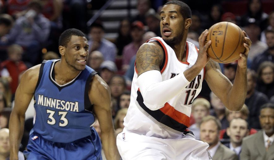 Portland Trail Blazers forward LaMarcus Aldridge looks for an opening as Minnesota Timberwolves forward Thadeus Young, left, defends during the first half of an NBA basketball game  in Portland, Ore., Sunday, Nov. 30, 2014. (AP Photo/Don Ryan)