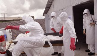 In this photo taken on Friday, Nov. 28, 2014, health workers wearing Ebola protective gear remove the body of a man they suspect died from the Ebola virus, at a USAID, American aid Ebola treatment center at Tubmanburg on the outskirts of  Monrovia, Liberia. (AP Photo/ Abbas Dulleh) ** FILE **