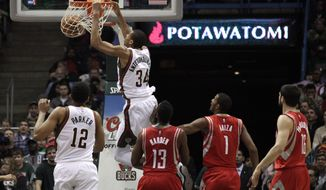Milwaukee Bucks guard Giannis Antetokounmpo (34) slam-dunks against the Houston Rockets during the first half of an NBA basketball game Saturday, Nov. 29, 2014, in Milwaukee. (AP Photo/Darren Hauck)