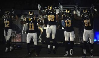 Members of the St. Louis Rams raise their arms as they walk onto the field during introductions before an NFL football game against the Oakland Raiders, Sunday, Nov. 30, 2014, in St. Louis. (AP Photo/L.G. Patterson)