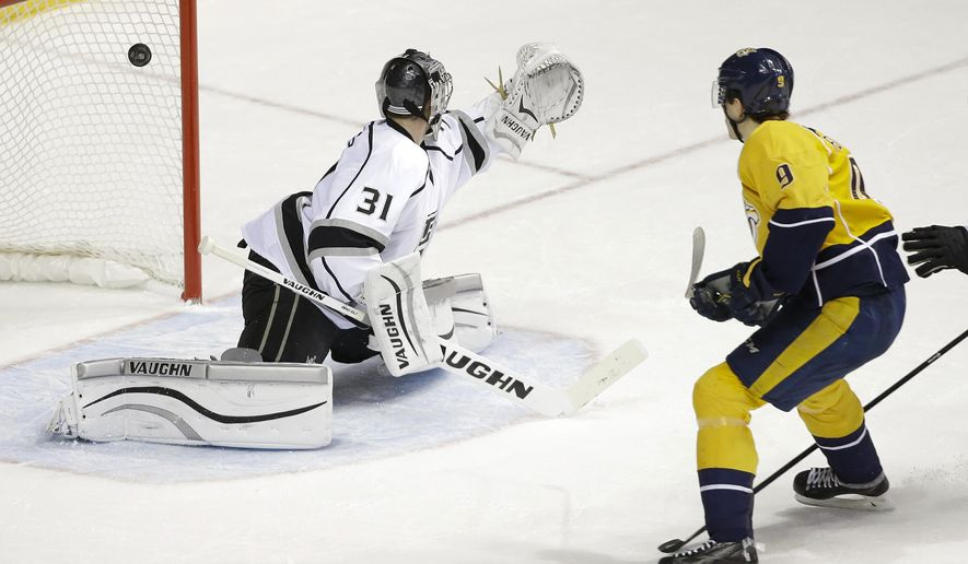 Los Angeles Kings goalie Martin Jones (31) reaches for a shot that hits the goalpost as Nashville Predators center Filip Forsberg (9), of Sweden, closes in during overtime at an NHL hockey game Tuesday, Nov. 25, 2014, in Nashville, Tenn. The Predators won 4-3 in a shootout. (AP Photo/Mark Humphrey)