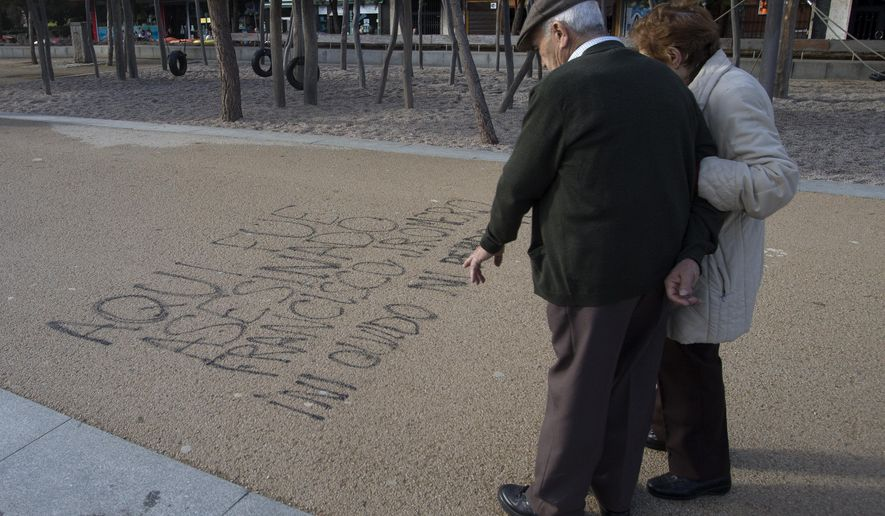 A couple stop to look at words painted on the ground by the Manzanarez river near where a 43-year-old Deportivo fan was killed, Madrid, Spain, Monday, Dec. 1, 2014. The man died and 11 others suffered minor injuries after a fight broke out across the river from Atletico de Madrid's soccer stadium between its fans and those of visiting team Deportivo La Coruna on Sunday. Madrid's Clinico San Carlos hospital said a man died of injuries sustained in the clash between rival fans that broke out hours before the game near the Vicente Calderon stadium and had to be removed from the river. Police made several arrests. Writing in Spanish reads: 'Here, Francisco J. Romero was murdered. I will never forget or Forgive' (AP Photo/Paul White)