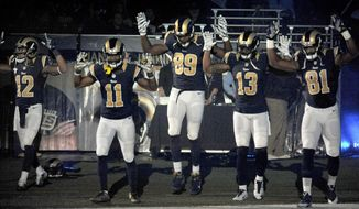 In this Sunday Nov. 30, 2014, file photo, St. Louis Rams players, from left; Stedman Bailey (12), Tavon Austin (11), Jared Cook, (89) Chris Givens (13) and Kenny Britt (81) raise their arms in awareness of the events in Ferguson, Mo.,  as they walk onto the field during introductions before an NFL football game against the Oakland Raiders in St. Louis. (AP Photo/L.G. Patterson, File)