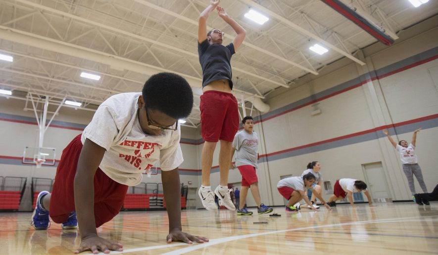 In this Oct. 30, 2014 photo, Jamal Barnett, 16, does burpees with his class during the physical education portion of the crime scene investigation course at Jefferson High School in Rockford, Ill. The course being piloted at Jefferson is exposing students to a potential career in law enforcement. (AP Photo/Rockford Register Star, Max Gersh)  MANDATORY CREDIT