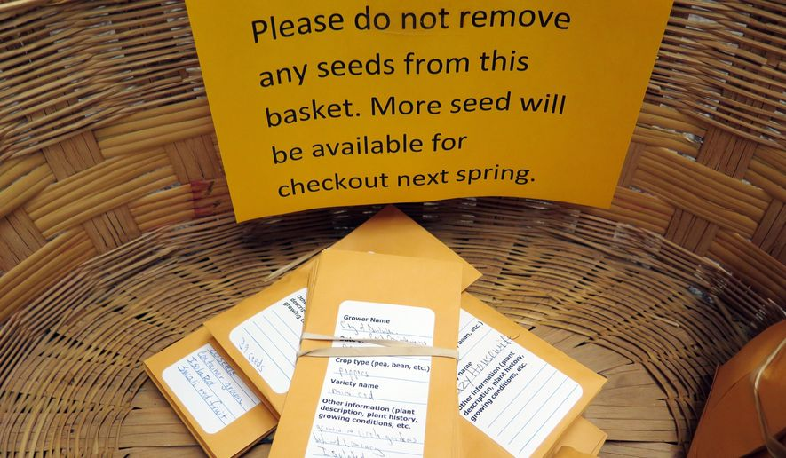 In this Nov. 26, 2014 photo, packets of seeds lay in a basket, part of a Duluth seed sharing program, at the Duluth Public Library in Duluth, Minn. Minnesota agriculture officials say the seed-sharing program at the Duluth library is on the wrong side of the law. The seed exchange, one of about 300 such programs in the U.S., allows members to borrow vegetable seeds from the library in the spring and later return seeds they collect from their gardens. The Minnesota Department of Agriculture caught wind of the program and has informed the library it is likely violating state seed law.  (AP Photo/Minnesota Public Radio, Dan Kraker)