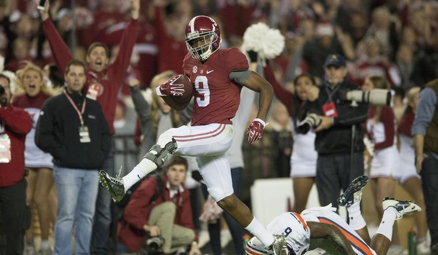 Alabama wide receiver Amari Cooper (9) scores a 75-yard touchdown reception as Auburn defensive back Jonathon Mincy (6) attempts to tackle him during an NCAA college football game, Saturday, Nov. 29, 2014 in Tuscaloosa, Ala. (AP Photo/The Montgomery Advertiser, Albert Cesare)  NO SALES