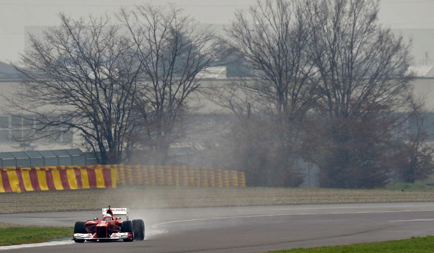 Sebastian Vettel steers an F2012 car from two seasons ago, at Ferrari's private Fiorano circuit, Italy, Saturday, Nov. 29, 2014. Sebastian Vettel is testing with Ferrari for the first time since signing with the Formula One team. It was announced last week that Vettel, who won four consecutive F1 titles at Red Bull, had signed a three-year deal with Ferrari to replace Fernando Alonso. (AP Photo/Marco Vasini)