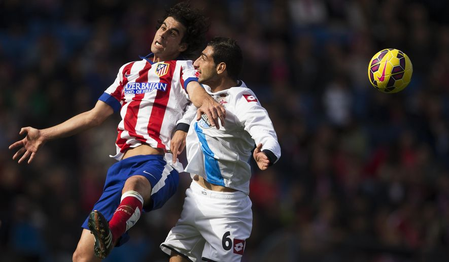 Atletico's Tiago, left, in action with Coruna's Jose Rodriguez, right, during a Spanish La Liga soccer match between Atletico and Deportivo Coruna at the Vicente Calderon stadium in Madrid, Spain, Sunday, Nov. 30, 2014. (AP Photo/Andres Kudacki)
