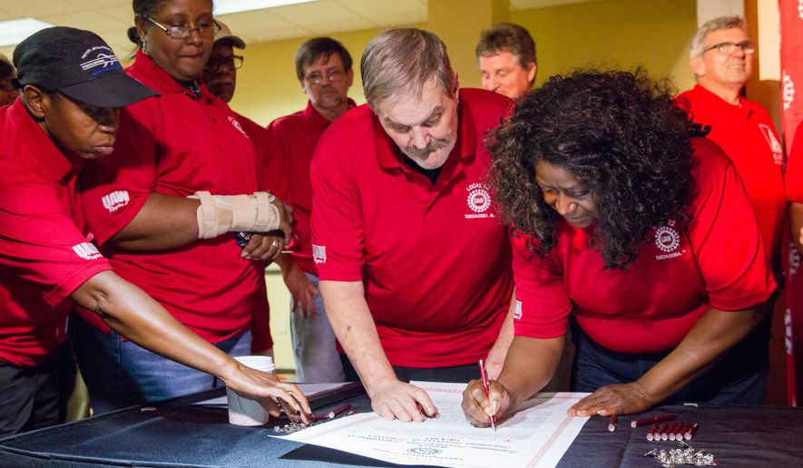 FILE - In this Oct. 3, 2014, file photo, Mercedes workers sign up for a new United Auto Workers local aimed at gaining representation at the Mercedes plant near Tuscaloosa, Ala. The National Labor Relations Board on Wednesday, Nov. 26, 2014 upheld a ruling that Mercedes violated federal labor laws by stopping United Auto Workers union supporters from handing out literature inside its Alabama plant. (AP Photo/Erik Schelzig, File)
