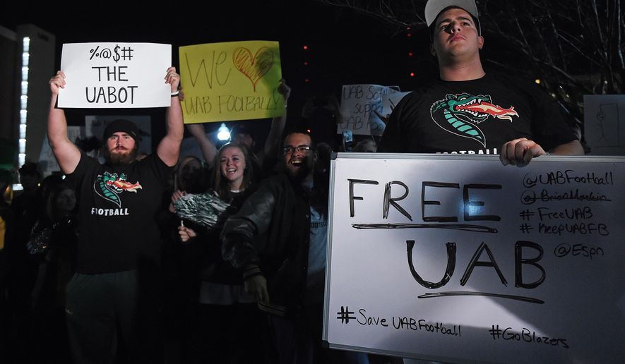 UAB football player Dominic Sylvester, right, and other players, alumni, students and supporters attend a rally to save the football program on the campus, in Birmingham, Ala., Sunday, Nov. 30, 2014. They came together amid controversy over the fate of UAB's football program. (AP Photo/Tamika Moore, AL.com)