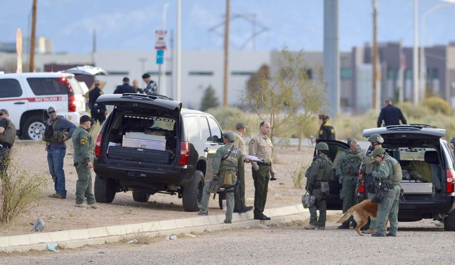 The Albuquerque Police department stages during the hunt for an active shooter in south west Albuquerque, New Mexico, Monday Dec. 1, 2014.  (AP Photo/Albuquerque Journal, Roberto Rosales)