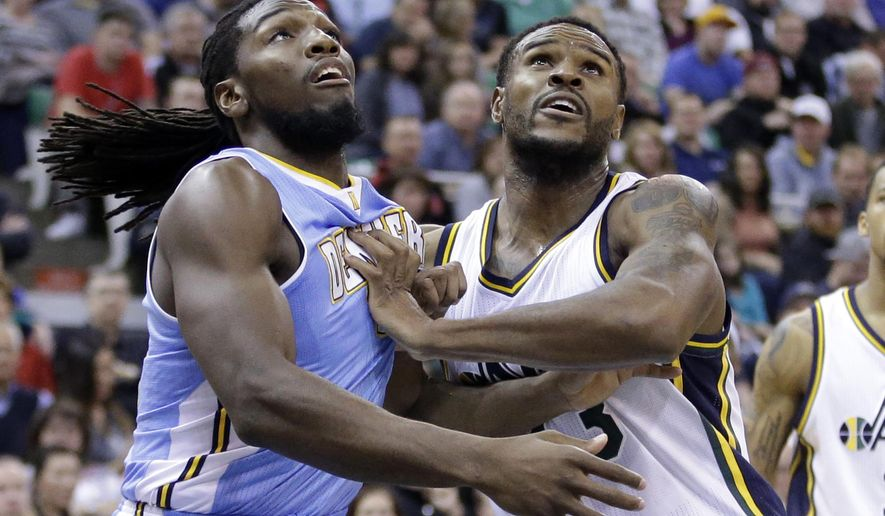 Denver Nuggets' Kenneth Faried, left, and Utah Jazz's Trevor Booker, right, battle for position under the boards in the second quarter during an NBA basketball game Monday, Dec. 1, 2014, in Salt Lake City. (AP Photo/Rick Bowmer)
