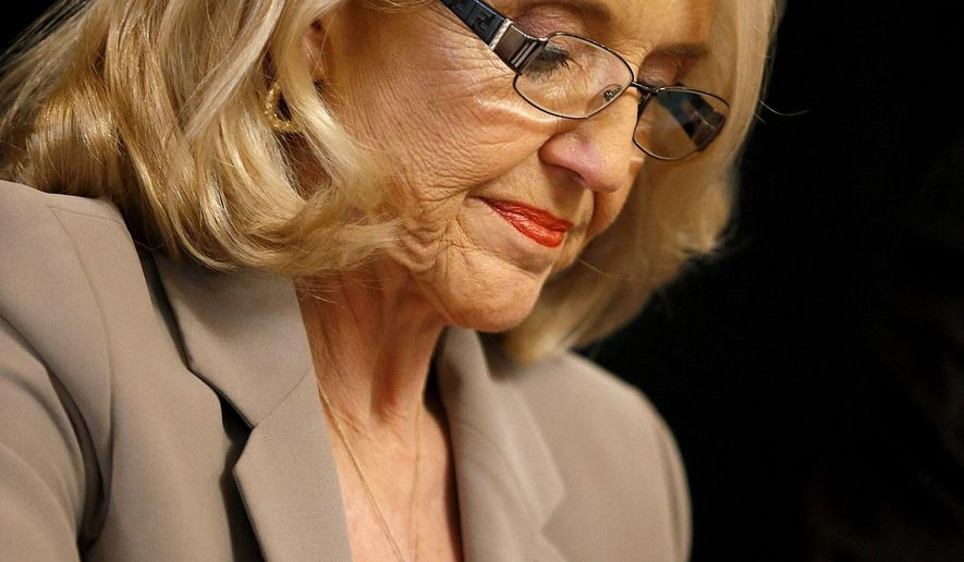 Gov. Jan Brewer signs the official election canvass for certification from the Nov. 4 general election results at the Arizona Capitol Monday, Dec. 1, 2014, in Phoenix. (AP Photo/Ross D. Franklin)