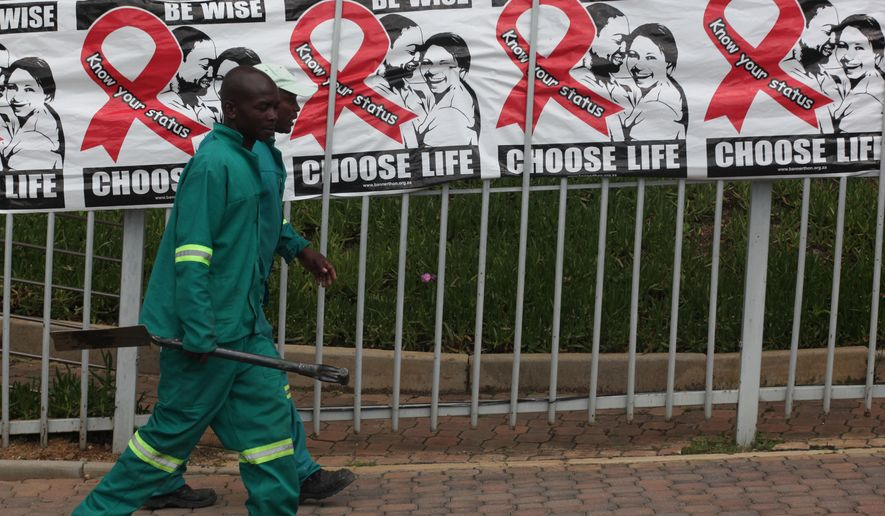 Gardeners pass World AIDS Day banners on the perimeter of an office building in Sandton, Johannesburg, South Africa, Monday, Dec. 1, 2014. About 2 million HIV-infected people are on government supplied ARV's with stigma related to the disease being a major issue according to the Treatment Action Campaign (TAC) who fought for the government funded drugs. (AP Photo/Denis Farrell)