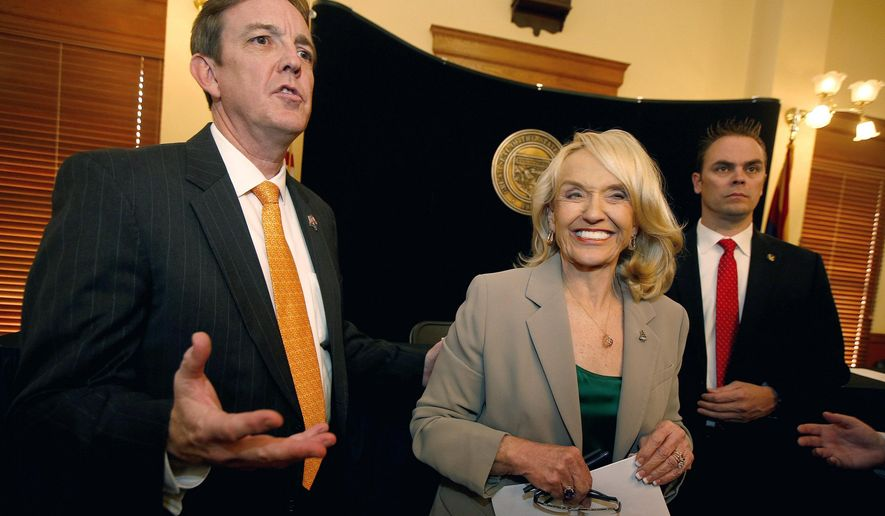 Secretary of State Ken Bennett, left, and Gov. Jan Brewer, center, talks about the election canvass certification for the results of the Nov. 4 general election after a signing ceremony at the Arizona Capitol Monday, Dec. 1, 2014, in Phoenix. (AP Photo/Ross D. Franklin)