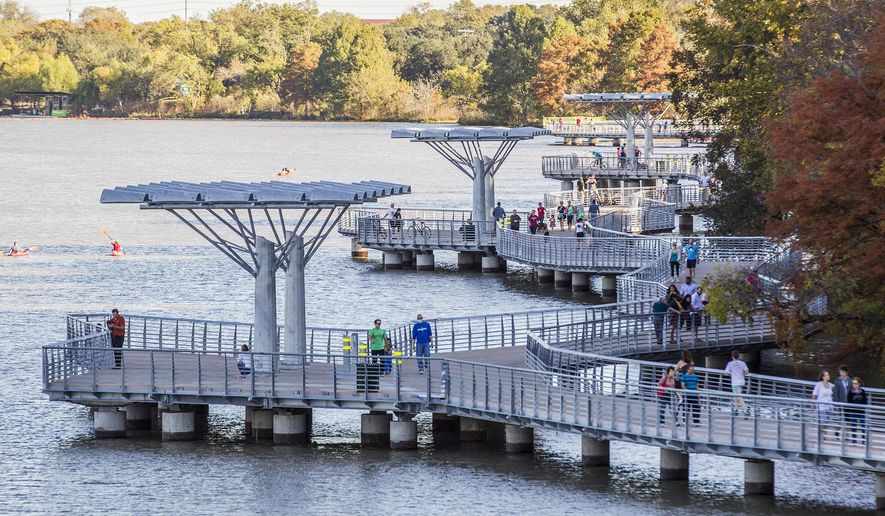 In this Sunday, Nov. 23, 2014 photo, joggers and walkers make their way on the Ann and Roy Butler Hike-and-Bike Trail at Lady Bird Lake, in Austin, Texas. A law proposed by Austin officials would result in fines of up to $500 for anglers caught fishing from the city's $28.1 million boardwalk along Lady Bird Lake. (AP Photo/Austin American-Statesman, Ricardo Brazziell)
