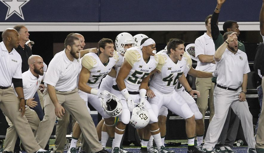 Members of the Baylor team cheer on their teammates in the closing minutes against Texas Tech in an NCAA college football game, Saturday, Nov. 29, 2014, in Arlington, Texas. Baylor won the game 48-46.  (AP Photo/Tim Sharp)