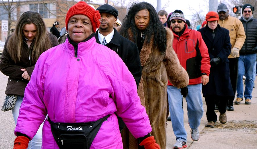 Hazel Joplin, second from left, who said she had never done anything like this before, and others walk down Division Drive during a silent march in Battle Creek, Mich., Monday, Dec. 1, 2014, which protested events in Ferguson, Mo. Protesters across the U.S. have walked off their jobs or away from classes in support of the Ferguson protesters.  Monday's walkouts stretched from New York to San Francisco, and included Chicago and Washington, D.C. The walkouts came a week after a St. Louis County prosecutor's announcement that a grand jury had decided not to indict white Ferguson police officer Darren Wilson in the August shooting death of 18-year-old Michael Brown, who was unarmed and black.  (AP Photo/Battle Creek Enquirer, John Grap)