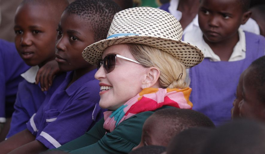U.S singer Madonna poses for a  picture with children in Kasungu, about 150 kilometers north of the capital Lilongwe, Sunday, Nov. 30, 2014. Madonna is currently visiting Malawi with her son David and daughter Mercy, where she has been working since 2006 with her non profit organization, Raising Malawi. (AP Photo/Tsvangirayi Mukwazhi)