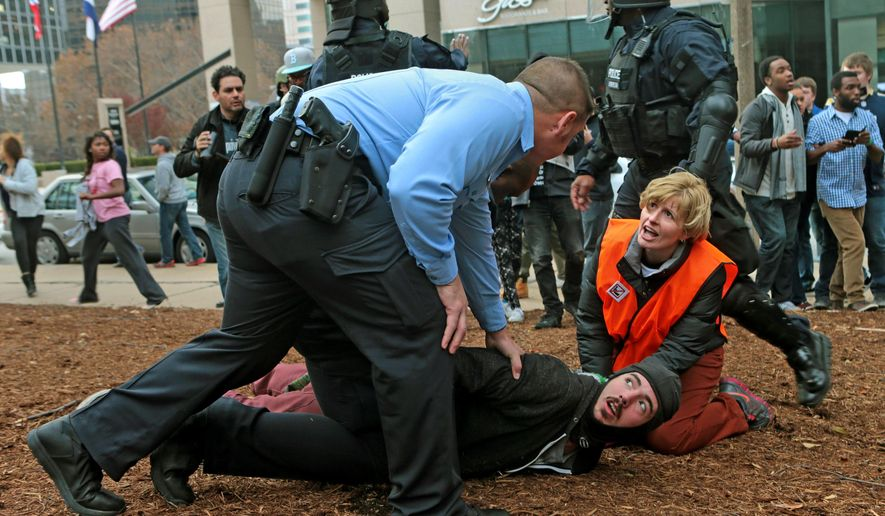 A clergy member assists a protester as he is taken to the ground on Sunday, Nov. 30, 2014, at Kiener Plaza in St. Louis. Protesters and police clashed following an NFL football game between the St. Louis Rams and the Oakland Raiders as protests continued following a grand jury's decision not to indict a Ferguson police officer in the shooting death of Michael Brown. (AP Photo/St. Louis Post-Dispatch, Laurie Skrivan)  EDWARDSVILLE INTELLIGENCER OUT; THE ALTON TELEGRAPH OUT