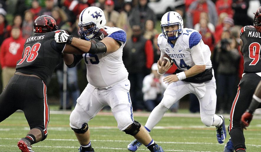 Kentucky quarterback Patrick Towles, right, attempts to run the ball during the second half of an NCAA college football game against Louisville, Saturday, Nov. 29, 2014, in Louisville, Ky. Louisville defeated Kentucky 44-40, and at left is Louisville's Sheldon Rankins, and Kentucky's Zach West, second from left. (AP Photo/Garry Jones)