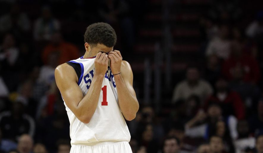 Philadelphia 76ers' Michael Carter-Williams wipes his face during a timeout in the second half of an NBA basketball game against the Philadelphia 76ers, Saturday, Nov. 29, 2014, in Philadelphia. Dallas won 110-103. (AP Photo/Matt Slocum)