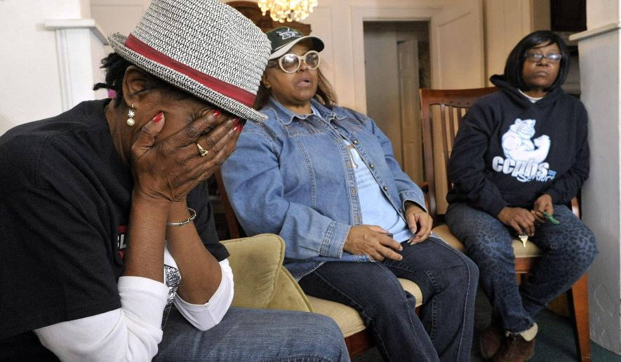 In this Nov. 19, 2014, from left, Emma Lockridge, 61, puts her head in her hands as she gets emotional while listening to stories of illness by Jacqueline Smith, 69, and Adrienne Crawford-Hill, 56, in Detroit. Some residents of a southwest Detroit neighborhood that's near an expanded Marathon oil refinery say they're stuck after not being included in a home buyout program. (AP Photo/Detroit News, Todd McInturf)