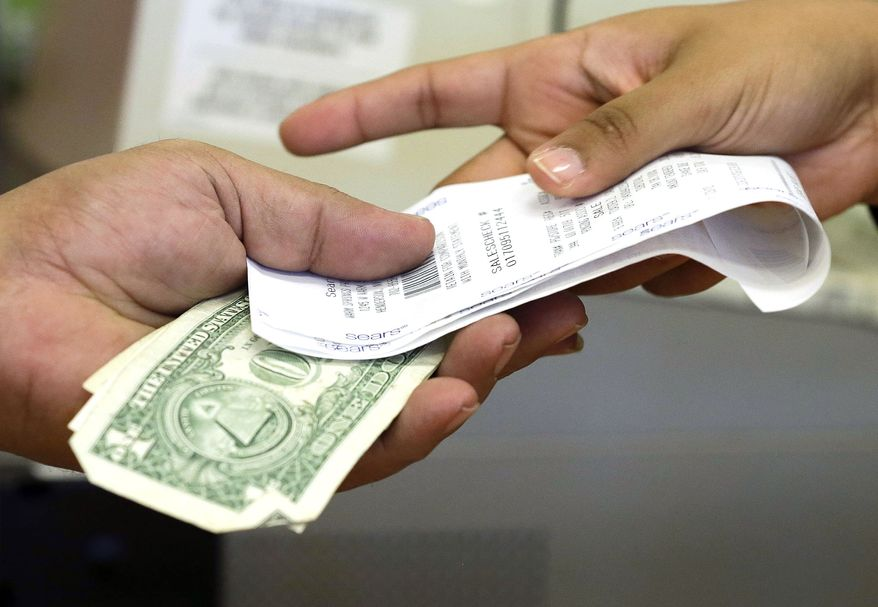 FILE - In this Friday, Nov. 23, 2012 file photo, a cashier hands a customer his change and receipt during a transaction at a Sears store, in Henderson, Nev. The University of Michigan issues its index of consumer sentiment for June, 2014 on Friday, June 27, 2014. (AP Photo/Julie Jacobson, File) **FILE**