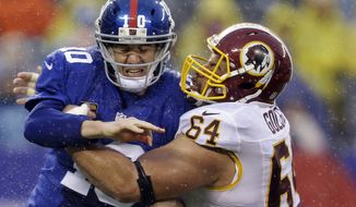 Washington Redskins defensive end Kedric Golston (64) hits New York Giants' Eli Manning (10) who throws a pass during the first half of an NFL football game on Sunday, Dec. 29, 2013, in East Rutherford, N.J.  (AP Photo/Julio Cortez)
