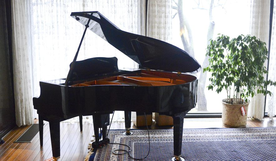 In this Nov. 24, 2014 photo, a Yamaha Mark III Disklavier piano, an acoustic piano with a MIDI-controlled device that turns the instrument into a player piano, is seen in Grand Rapids, Mich. The estate of former Steelcase Inc. chairman Peter Wege is auctioning off items from the late philanthropist's home in East Grand Rapids. Wege was a major donor to the Grand Rapids Art Museum and other organization before he died in July at age 94. (AP Photo/The Grand Rapids Press, Emily Rose Bennett)