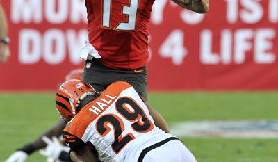 Tampa Bay Buccaneers wide receiver Mike Evans (13) is stopped by Cincinnati Bengals cornerback Leon Hall (29) during the fourth quarter of an NFL football game Sunday, Nov. 30, 2014, in Tampa, Fla. (AP Photo/Steve Nesius)