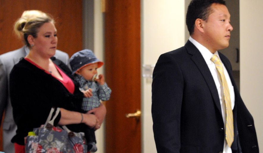 FILE - In this May 21, 2014 file photo, Marcus Kaarma, right, is followed into Missoula District Court by his wife Janelle with their child in Missoula, Mont. Jury selection began Monday, Dec. 1, 2014 in the trial of Kaarma, a Montana man charged with fatally shooting Diren Dede, a German exchange student who broke into his garage. (AP Photo/The Missoulian, Michael Gallacher, File)