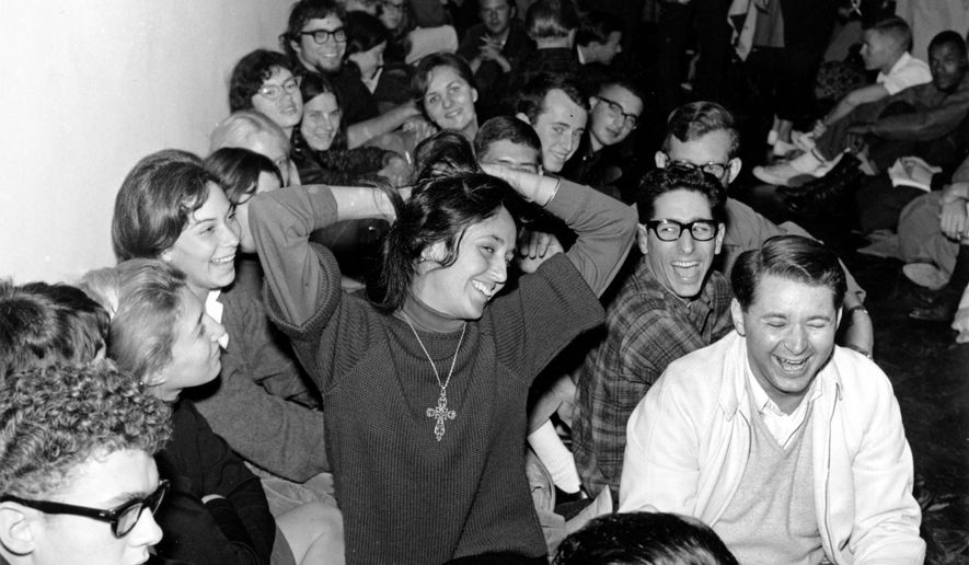 In this Dec. 2, 1964, file photo, folk singer Joan Baez clowns as she sits with student demonstrators in Sproul Hall on the University of California campus in Berkeley, Calif. The students, participating in a Free Speech Movement, will remain until disciplinary action is dropped against four self-styled free speech leaders.  This fall marks the 50th anniversary of the Free Speech Movement, a protest that only lasted for three months but set the stage for the turbulent 1960s. (AP Photo, File)