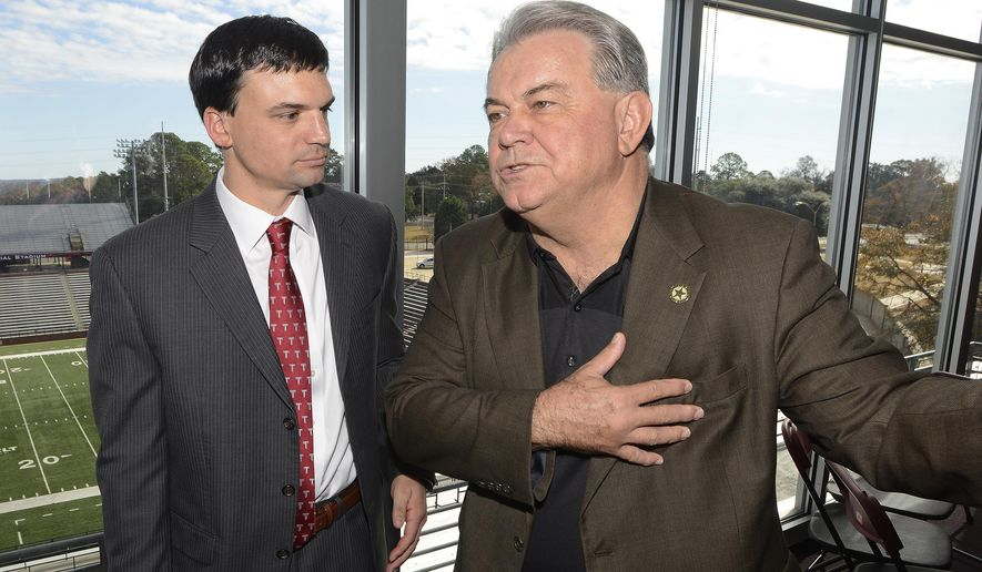 Former Troy University NCAA college head football coach Larry Blakeney, right, chats with new head football coach Neal Brown, left, after a news conference at Troy University on Monday Dec. 1, 2014, in Troy, Ala. (AP Photo/The Montgomery Advertiser, Mickey Welsh)  NO SALES