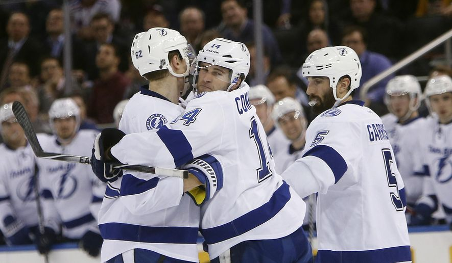Tampa Bay Lightning's Brett Connolly (14) celebrates with teammates Andrej Sustr (62), of Czech Republic, and Jason Garrison (5) after scoring against the New York Rangers during the first period of an NHL hockey game Monday, Dec. 1, 2014, in New York. (AP Photo/Jason DeCrow)