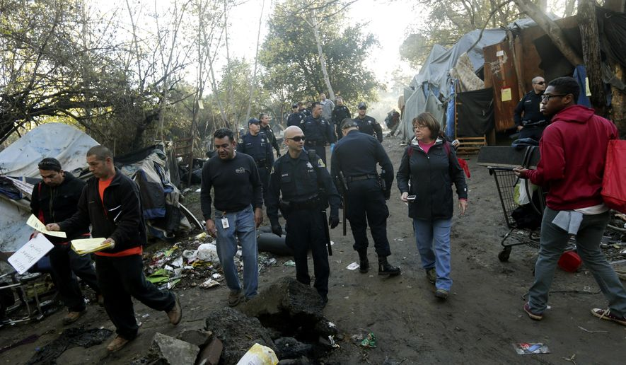 Police officers and city officials hand out warning notices at a Silicon Valley homeless encampment known as The Jungle, Monday, Dec. 1, 2014, in San Jose, Calif. City officials began posting notices on hand built structures, tents and tree trunks warning the 200 residents of what is likely the nation's largest homeless encampment that the bulldozers are coming. People living in the Silicon Valley camp, known as The Jungle, must be out by Thursday, Dec. 4 or face arrest for trespassing. (AP Photo/Marcio Jose Sanchez)
