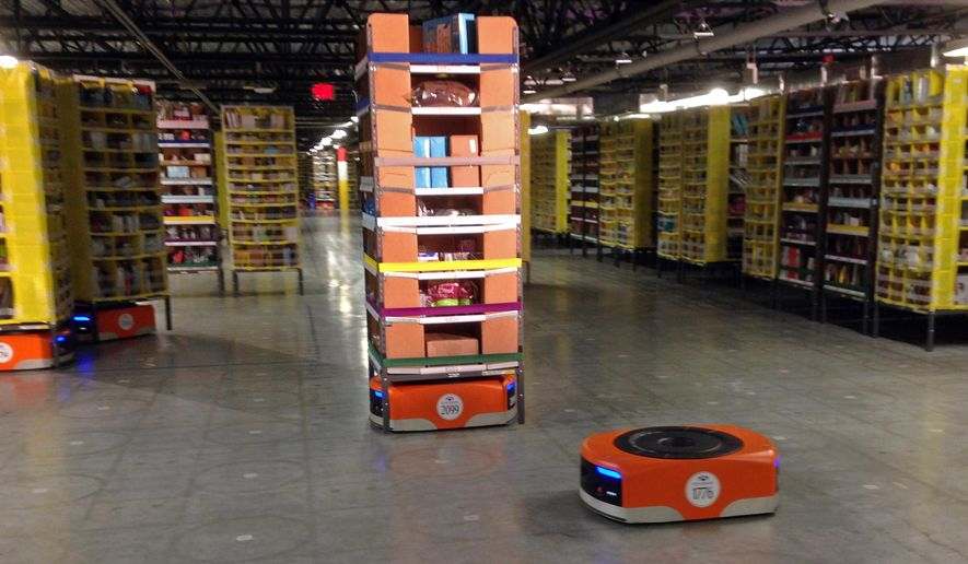 A Kiva robot drive unit is seen, foreground, before it moves under a stack of merchandise pods, seen on a tour of one of Amazon's newest distribution centers in Tracy, Calif., Sunday, Nov. 30, 2014. This Amazon Fulfillment Center opened in 2013 and was refitted to use new robot technology in the summer of 2014. All year Amazon has been investing in ways to make shipping faster and easier to prepare for this holiday season. At this Northern California warehouse the company is employing robotics and other new technology to help workers process the annual onslaught of shopping orders. (AP Photo/Brandon Bailey)