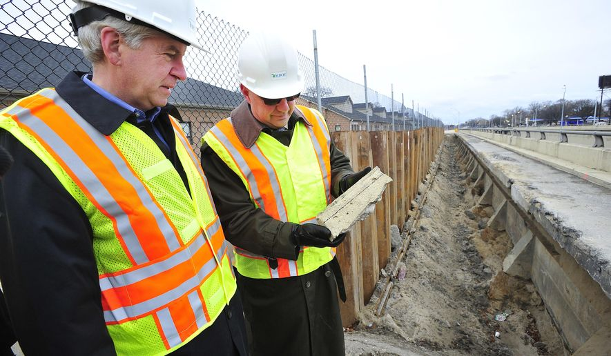 Michigan Department of Transportation Director Kirk Studle shows Michigan Gov. Rick Snyder a chunk of concrete that has broken free of the retaining wall as they look over a section of the Lodge Freeway between McNichols and Meyers that has seen deterioration in Detroit, on Monday, Dec. 1, 2014. (AP Photo/Detroit News, Daniel Mears)