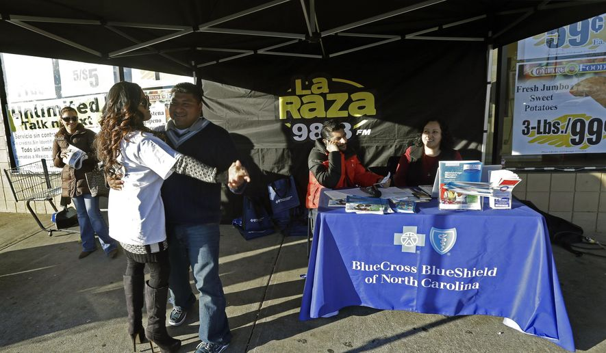 In this photo taken Saturday, Nov. 22, 2014, a couple dances as benefits agent Patricia Sarabia, right, while Blue Bridge Benefits LLC, and radio D.J. Cesar Montalvo try to attract customers to the Blue Cross Blue Shield display promoting Obama Care at Compare Foods in Winston-Salem, N.C. Such atypical approaches to selling health insurance policies are playing out across the country since the second round of open enrollment under the federal Affordable Care Act opened in mid-November. Insurance companies and some states are focusing heavily on signing up eligible Hispanics, a group that accounts for a large share of the nation's uninsured but largely avoided applying for coverage during the first full year the health care reform law was in effect. Hispanics accounted for just 11 percent of those who enrolled in the private policies sold during the initial sign-up period, which ended in March.  (AP Photo/Gerry Broome)