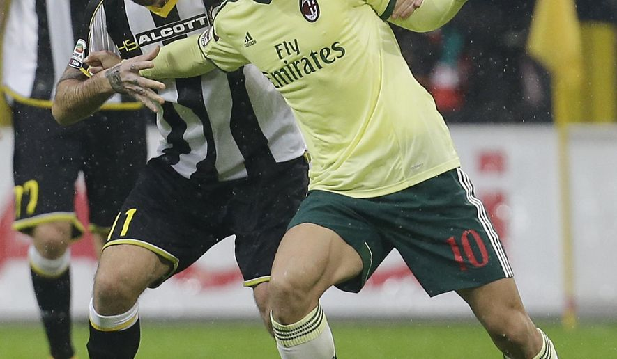 AC Milan's Keisuke Honda, right, challenges for the ball with Udinese's Maurizio Domizzi during the Serie A soccer match between AC Milan and Udinese at the San Siro stadium in Milan, Italy, Sunday, Nov. 30, 2014. (AP Photo/Antonio Calanni)