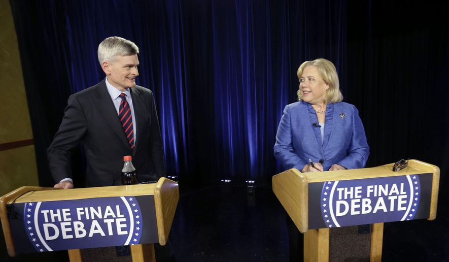 Sen. Mary Landrieu, D-La., right, and Rep. Bill Cassidy, R-La., greet each other before the start of their final debate for the Senate election runoff in Baton Rouge, La., Monday, Dec. 1, 2014. (AP Photo/Gerald Herbert)