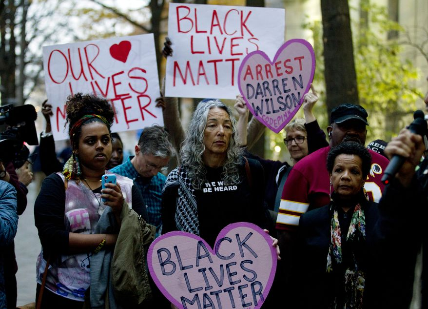 Demonstrators protest against the shooting of unarmed 18-year-old Michael Brown, during a rally at the Department of Justice in Washington, Monday, Dec. 1, 2014. A grand jury in Ferguson, Mo., on Monday, Nov. 24, 2014, declined to indict police officer Darren Wilson in the shooting death of Brown, an unarmed black man. Protesters across the U.S. have walked off their jobs or away from classes in support of the Ferguson protesters. Monday's walkouts stretched from New York to San Francisco, and included Chicago and Washington, D.C.  (AP Photo/Jose Luis Magana)