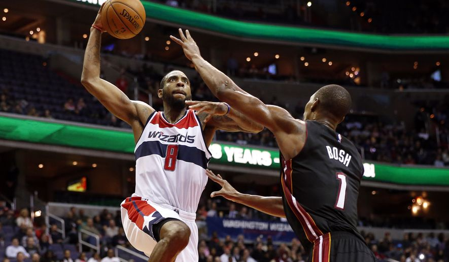 Washington Wizards forward Rasual Butler (8) prepares to dunk over Miami Heat center Chris Bosh (1) in the second half of an NBA basketball game, Monday, Dec. 1, 2014, in Washington. The Wizards won 107-86. (AP Photo/Alex Brandon)