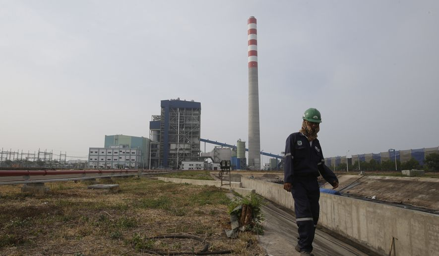 In this Oct. 17, 2014 photo, a worker walks at power plant area  in Cirebon. The sprawling power station that hums and coughs along this coast in Indonesia is labeled as a Japanese contribution to the global fight against climate change. The plants promote new coal technology from Japanese companies, which is cleaner than old coal technology but still pollutes far more than solar, wind or natural gas. Villagers nearby also complain that the coal plant is damaging the local environment, and that stocks of fish, shrimp and green mussels have dwindled. (AP Photo/Achmad Ibrahim)