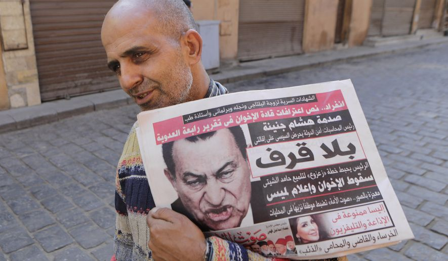 "An Egyptian man carries newspapers with a photo of former Egyptian President Hosni Mubarak on it, in Cairo, Egypt, Monday, Dec. 1, 2014. A judge dismissed murder charges Saturday, Nov. 29, against former President Hosni Mubarak and acquitted his security chief over the killing of protesters during Egypt's 2011 uprising, crushing any hope of a judicial reckoning on behalf of the hundreds victims of the revolt that toppled him. Protests are planned for Tuesday against the verdict. The headline on the newspaper in Arabic reads, ""enough already."" (AP Photo/Amr Nabil)"