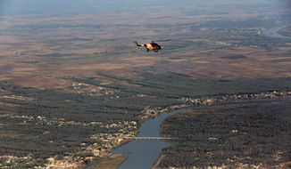 An Iraqi Army helicopter flies over the city of Baquba, the capital of Iraq's Diyala province, 35 miles (60 kilometers) northeast of Baghdad, Iraq. (AP Photo/Hadi Mizban)