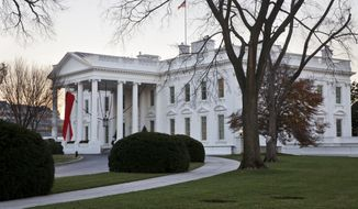 The White House in Washington is decorated with a red ribbon in honor of World AIDS Day, Monday, Dec. 1, 2014. (AP Photo/Jacquelyn Martin) **FILE **